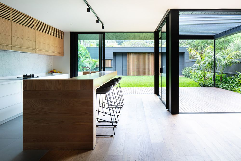 The kitchen, dining room and living area share an open floor plan with full-height windows that welcome the outdoors in