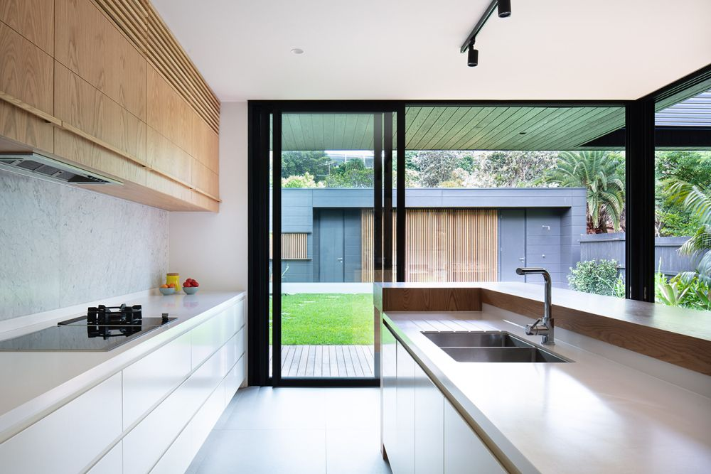 Glass doors provide access to the front and rear gardens, maximizing the connection between the spaces