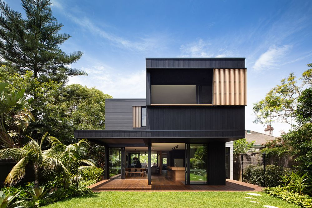 The exterior of the house is black with warm timber accents and large expanses of glass