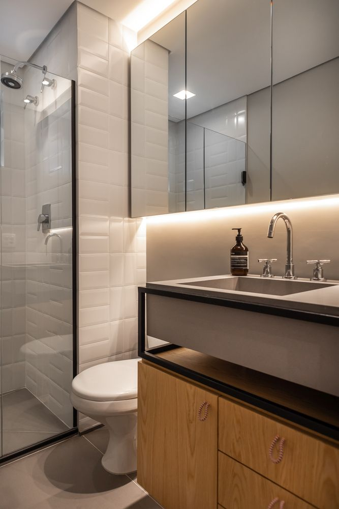 The bathroom, although small, looks bright and airy thanks to the lighting, glass and mirrors