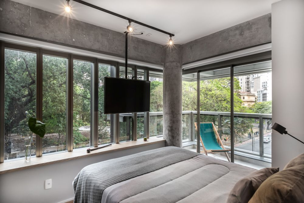 The bedroom has a surprising amount of windows as well as access to its own corner balcony