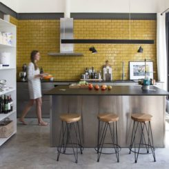 Stainless steel kitchen island and yellow subeay tiles