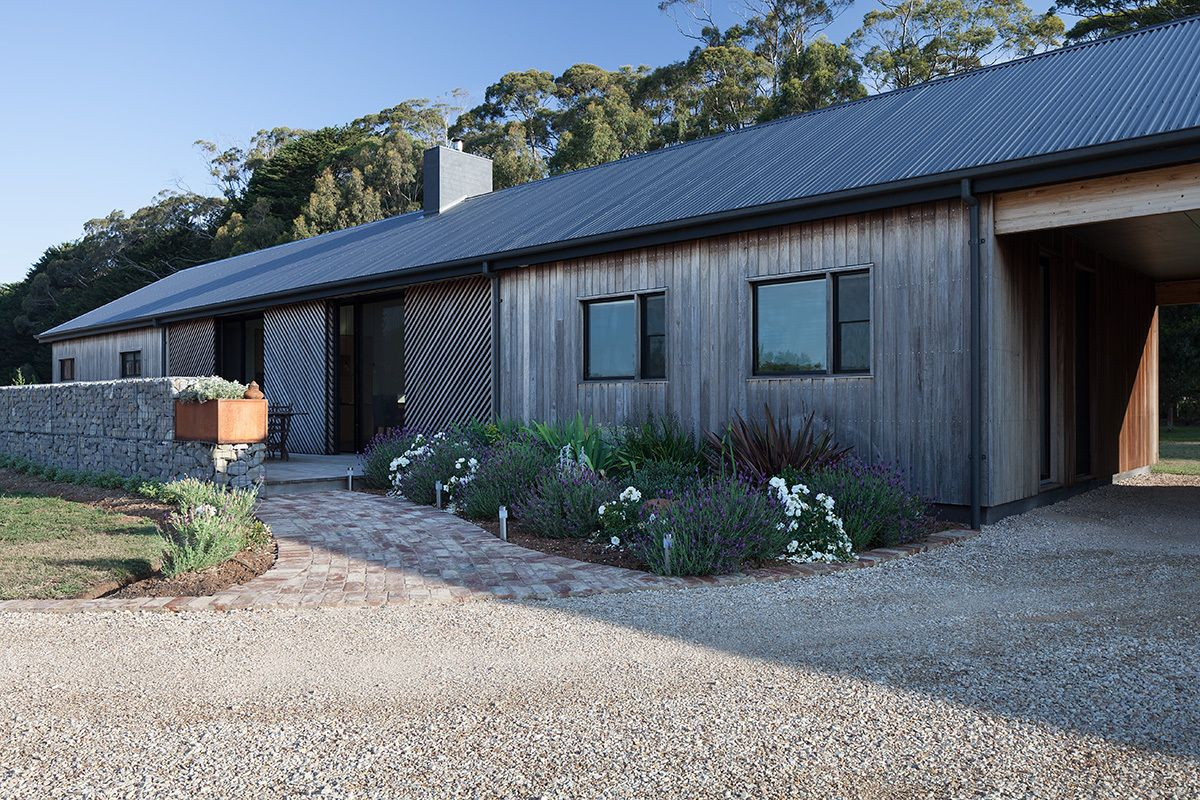The natural patina of the wood-clad facades helps the house blend in more easily