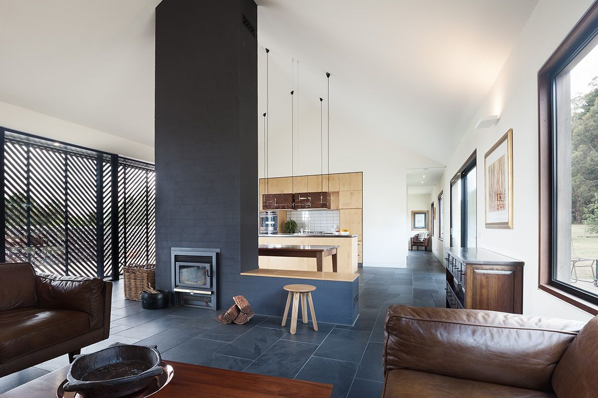 The living room, kitchen and dining area share an open floor plan with a fireplace wall doubling as a divider