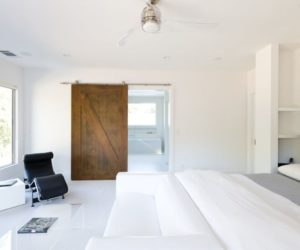 Bedroom with sliding barn door and white walls paint