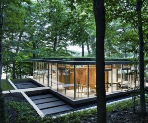 A Glass House Framed By A Lush Forest And A Beautiful Lake
