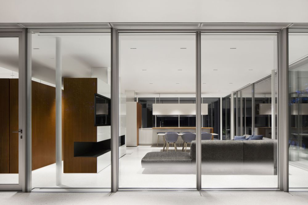 The living spaces are surrounded by glass walls and doors with thin frames which obstruct the views as little as possible