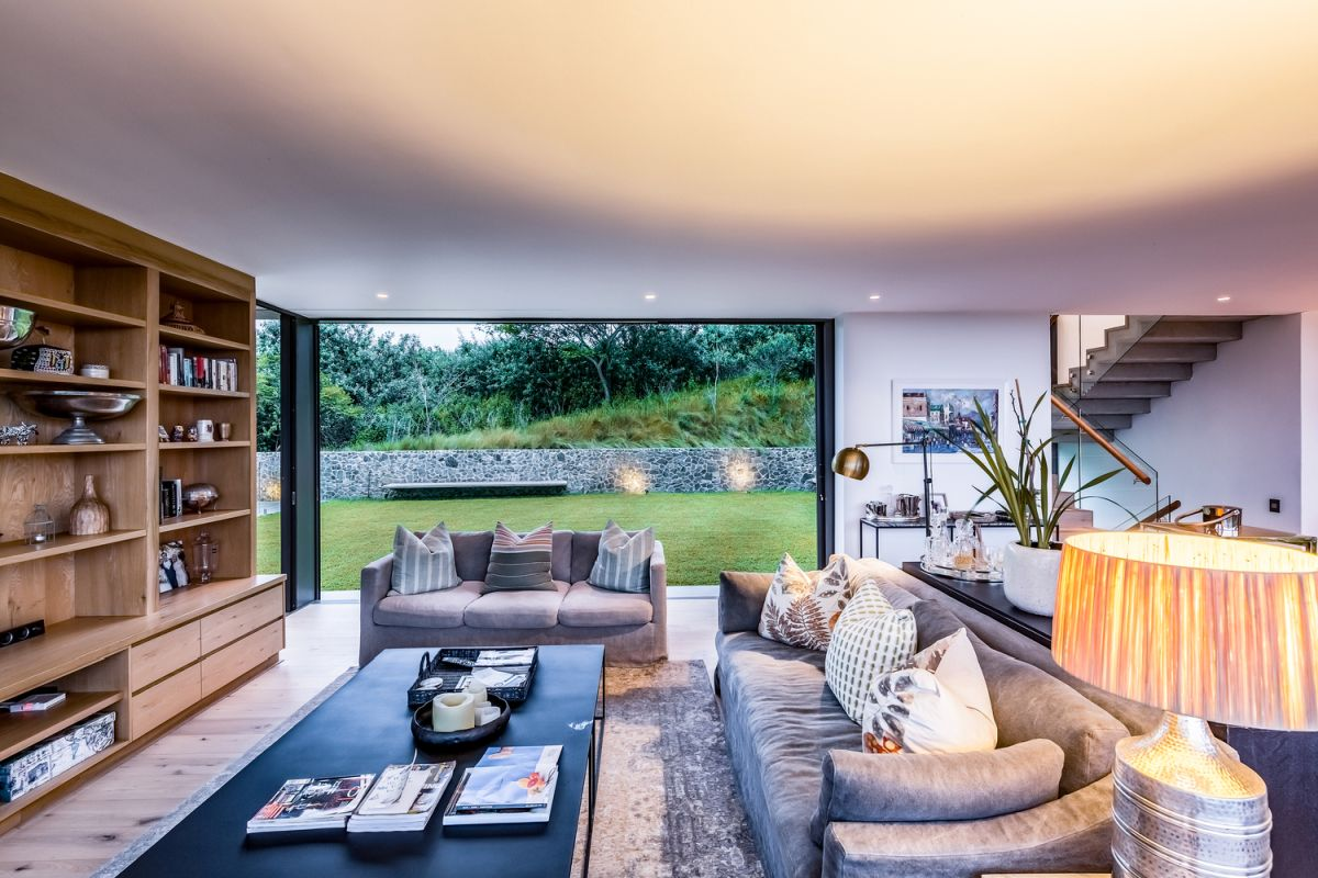 The ground floor spaces have sliding glass walls which seamlessly connect them to the garden