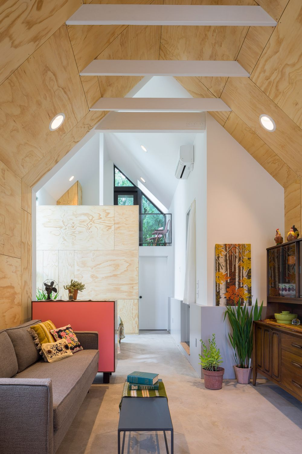 The light plywood surfaces create a warm and inviting ambiance while keeping the decor bright and simple