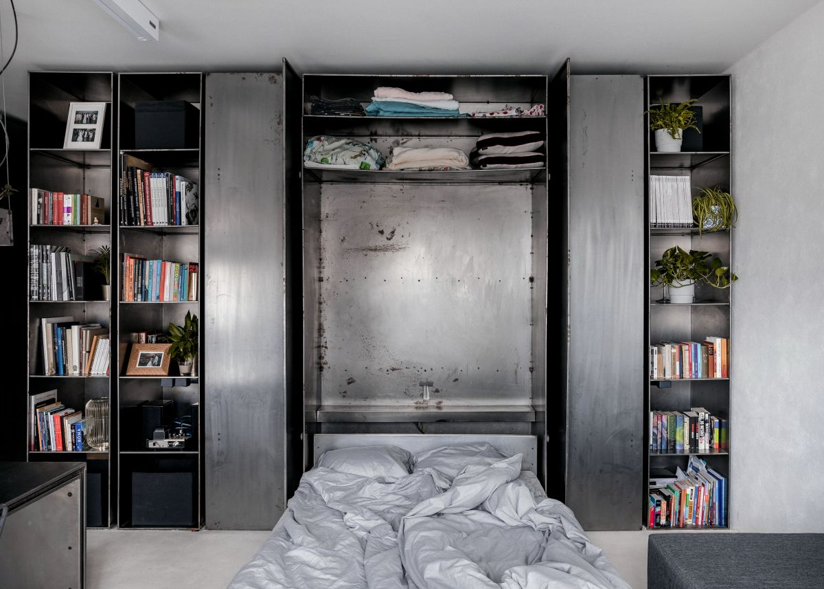 The bed can be stored vertically inside the custom wall unit, making the bedroom disappear completely