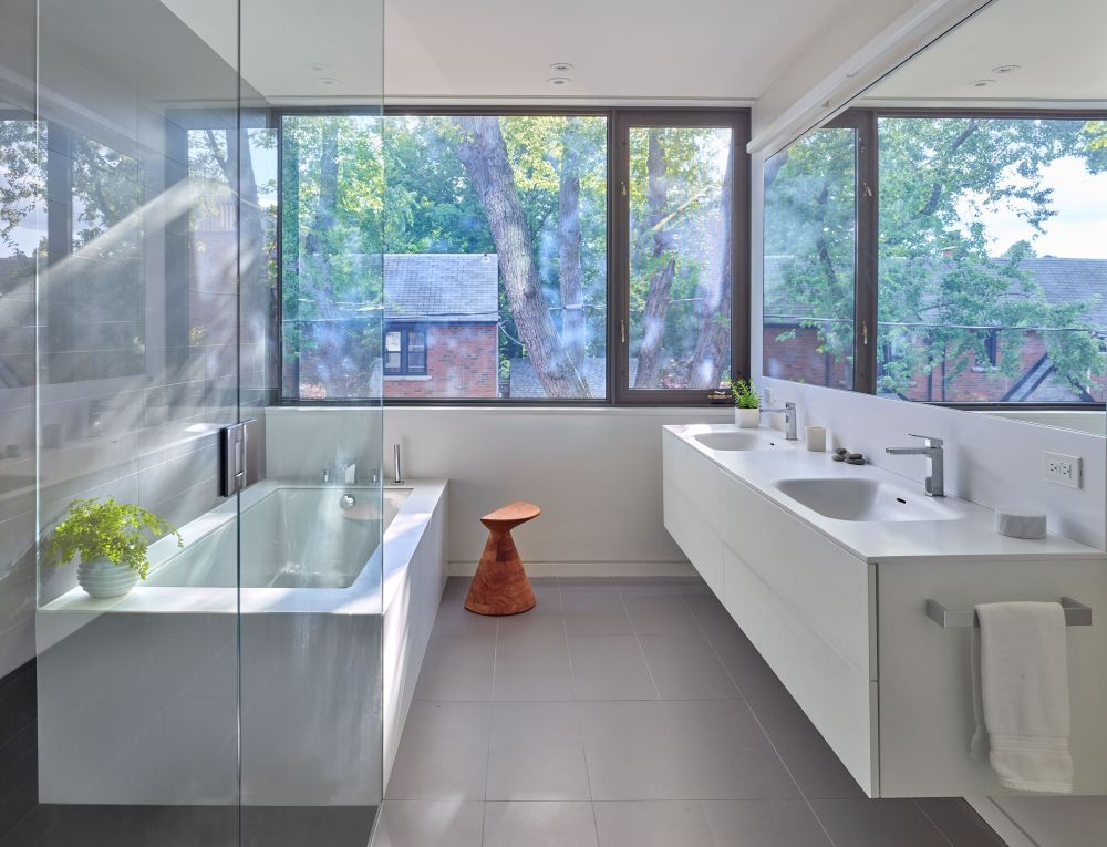 The bathroom is filled with natural light too and features large windows and glass partitions which take advantage of this