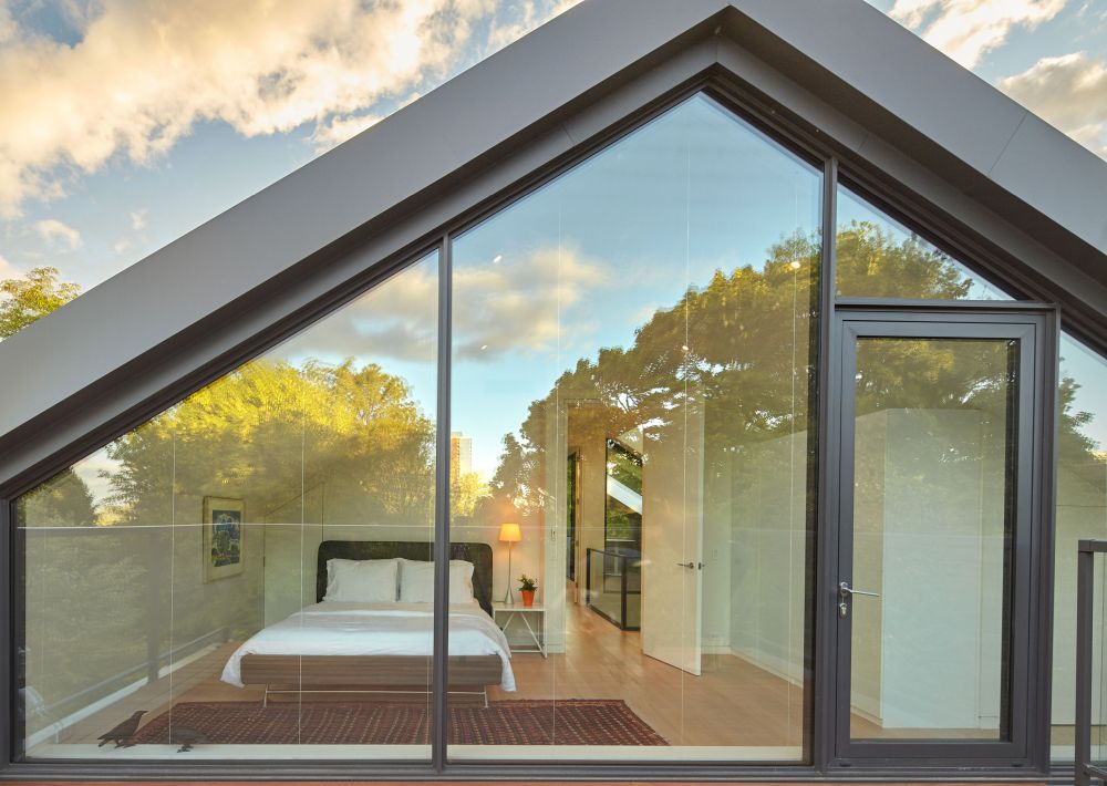 The master bedroom and the deck are separated by full-height glass panels which ensure a seamless connection