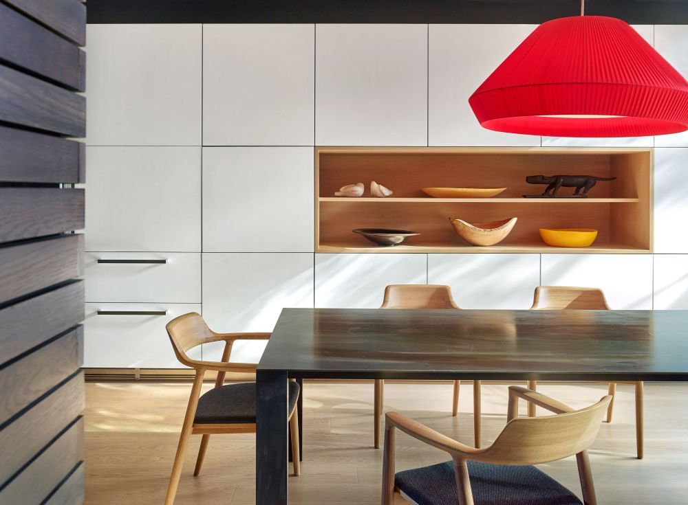 The dining room has light wooden flooring, white custom cabinetry and a bright red pendant lamp for contrast