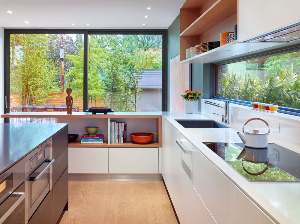 The kitchen is L-shaped, with windows on both sides and a practical island with built-in appliances