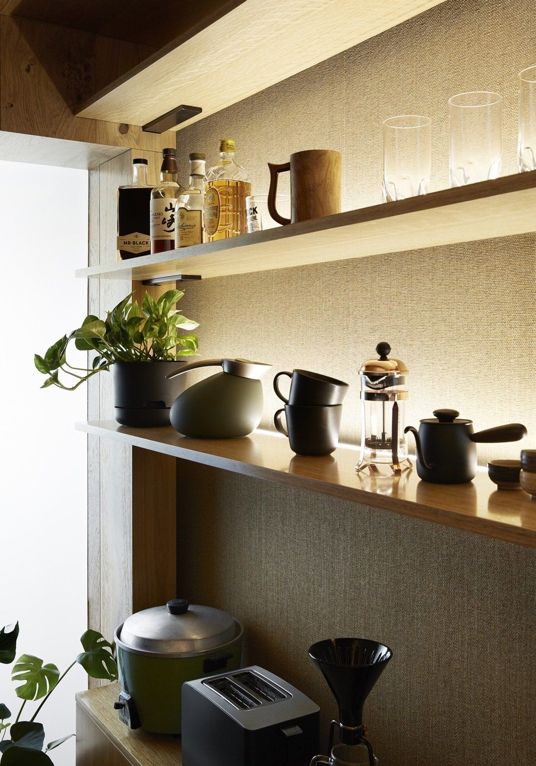 The timber surfaces and units featured throughout the apartment create a warm and inviting vibe