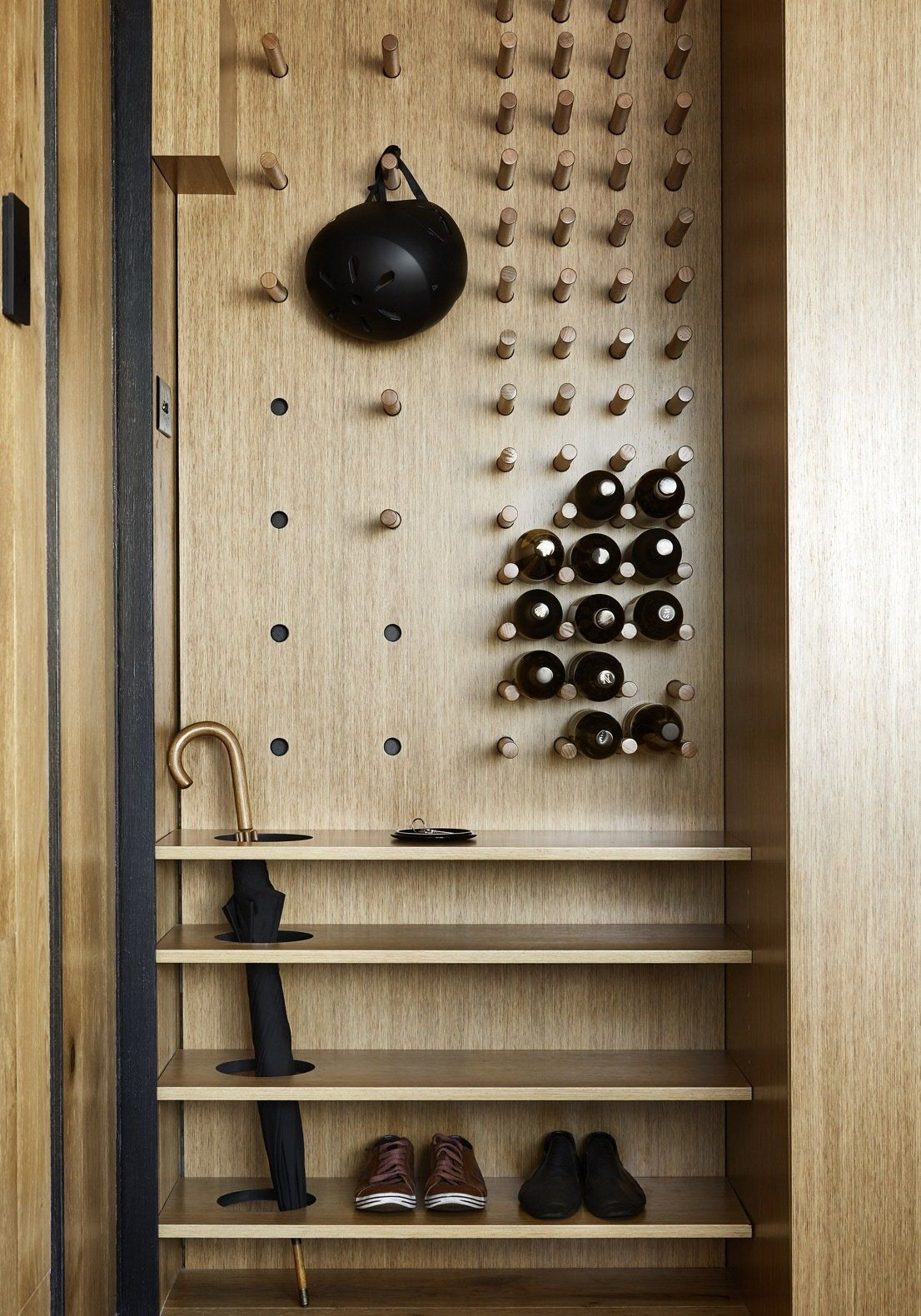 The entryway is small but very space-efficient, featuring a clever, custom-made storage unit with pegs, slots and shelves