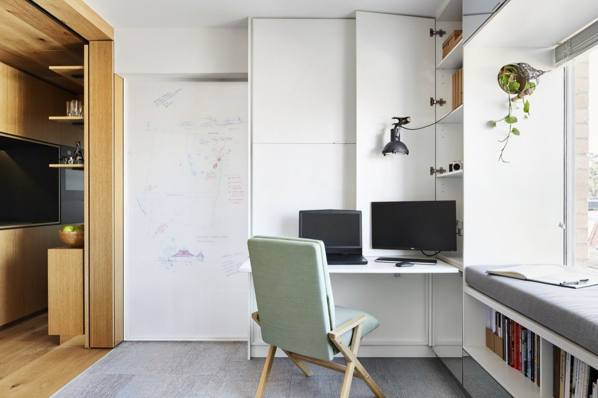 A small desk similar to a shelf is part of the living area, being situated next to the window bench