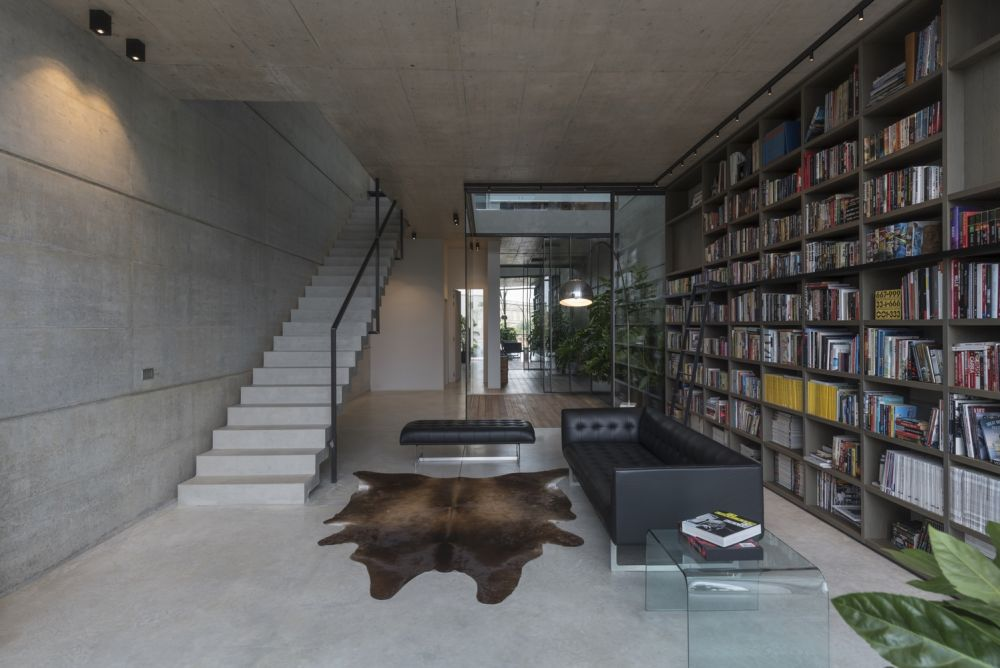 A large bookcase stretches over the living room wall creating an inviting decor and adding color to the space