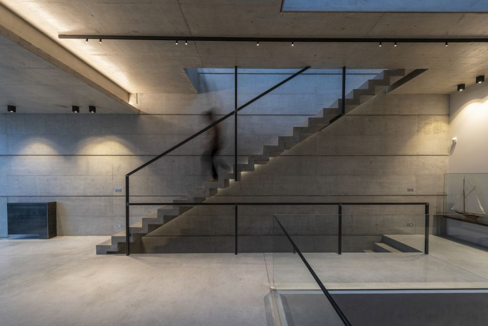 The floors are connected via a simple concrete staircase which also acts as a separator between various zones