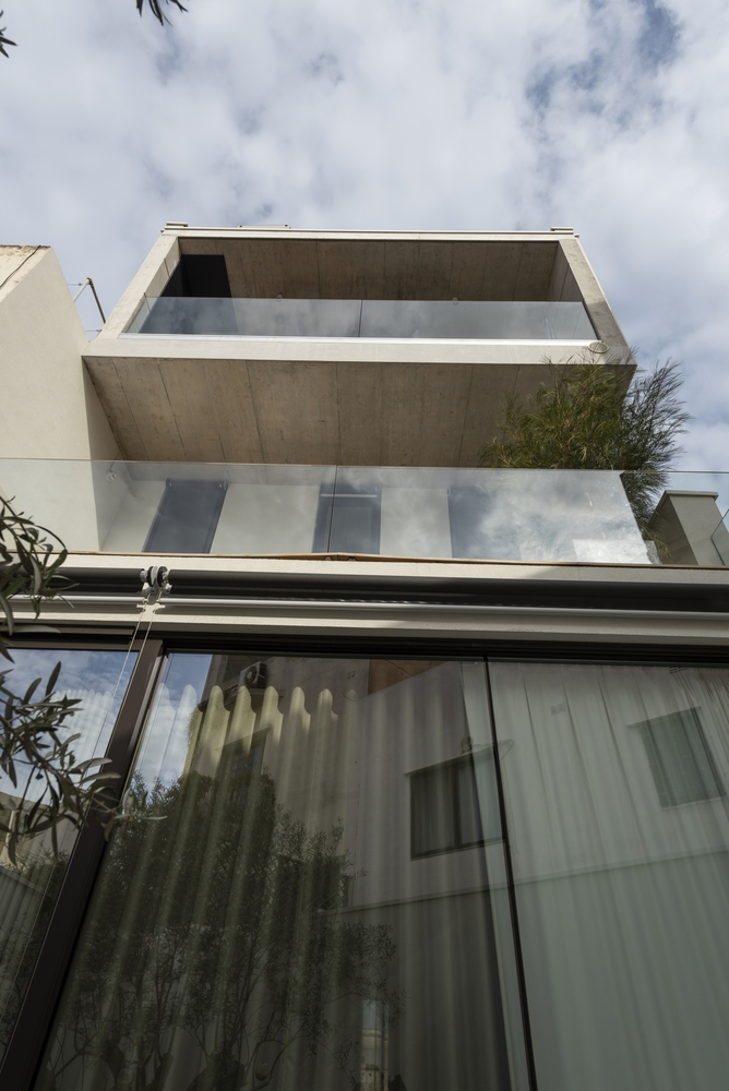 The glazed facade and glass railings give the house a contemporary appearance