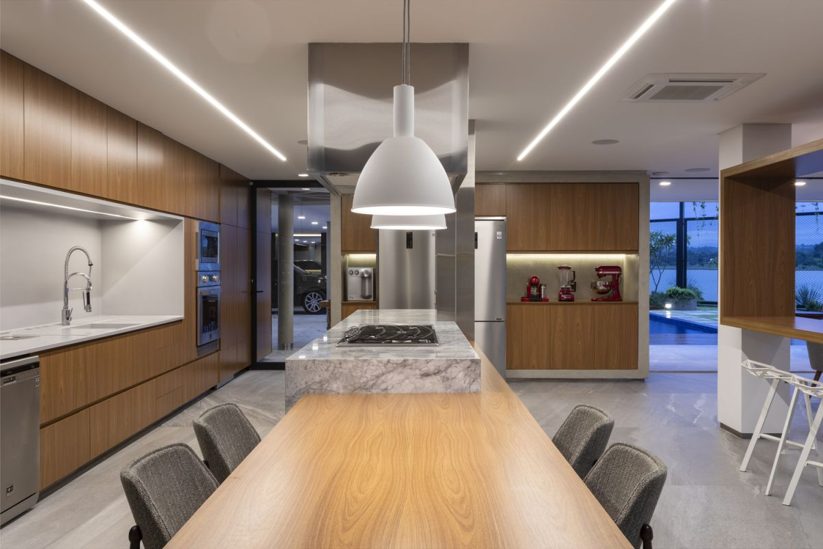The kitchen island extends into a dining table, with minimalist pendant lamps hanging from the ceiling