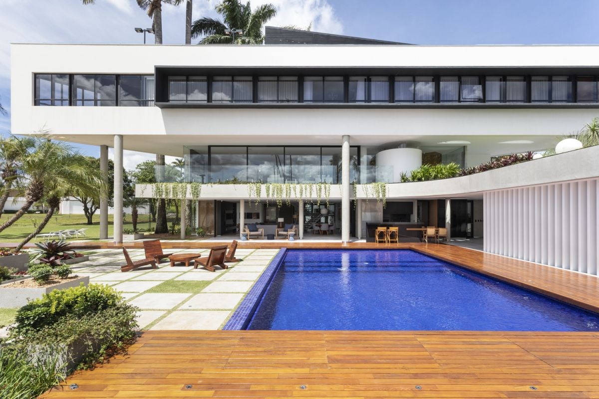 A wooden deck frames the pool and strengthens the bond between the indoor and the outdoor spaces