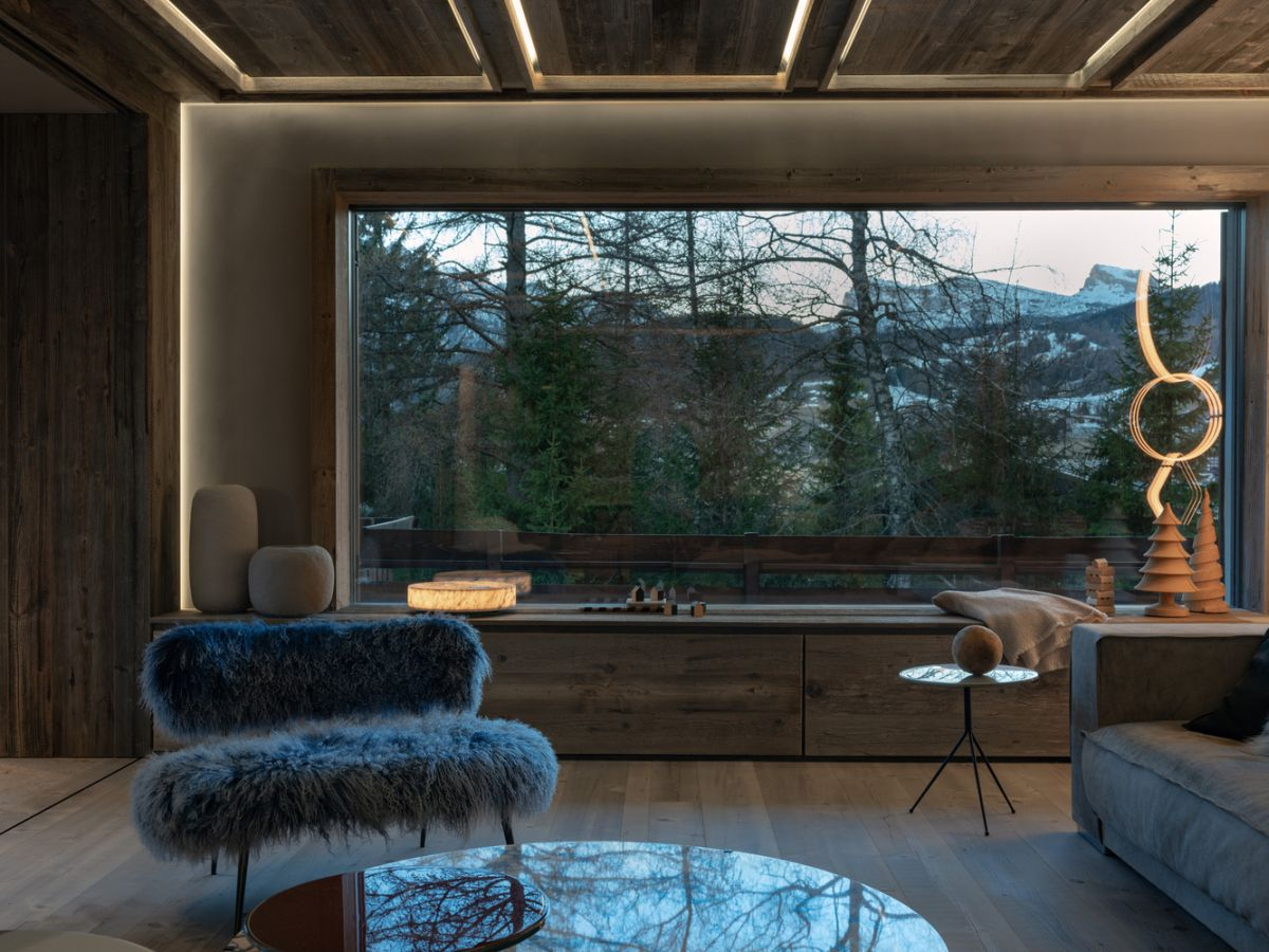 Large windows are framed by cozy seating nooks and benches that complete the decor in a charming manner
