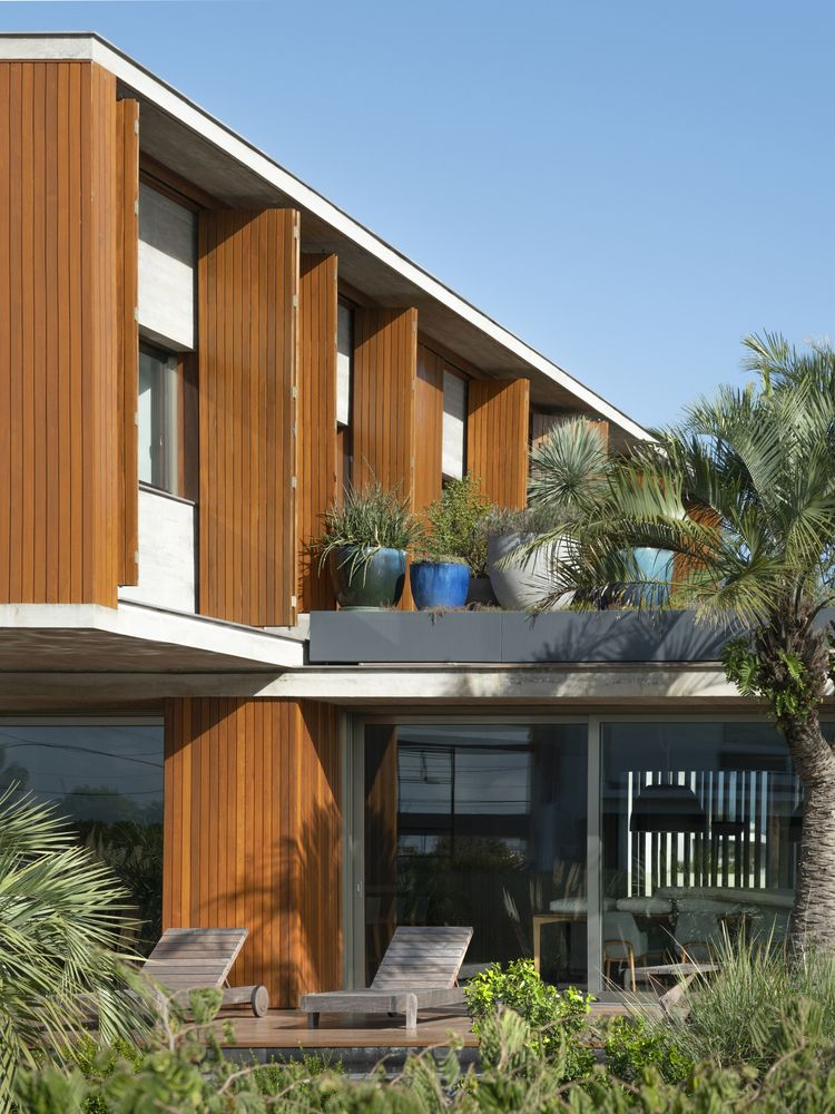 The cantilevered top floor forms a protective roof over the ground floor porch area