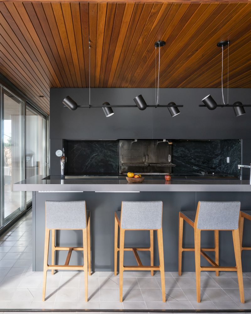 The kitchen is almost entirely grey, with minimalist furniture and a beautiful wooden ceiling