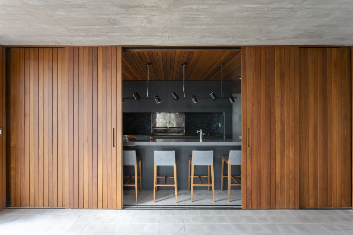 Sliding wooden panels can easily conceal the kitchen, separating it from the living area