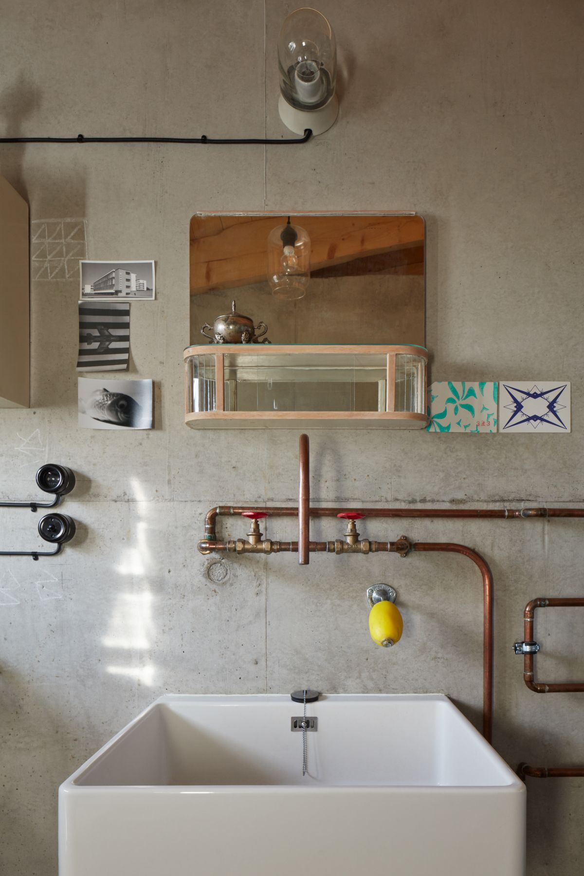 The en-suite bathroom has bare walls and exposed pipes which double as decorative elements