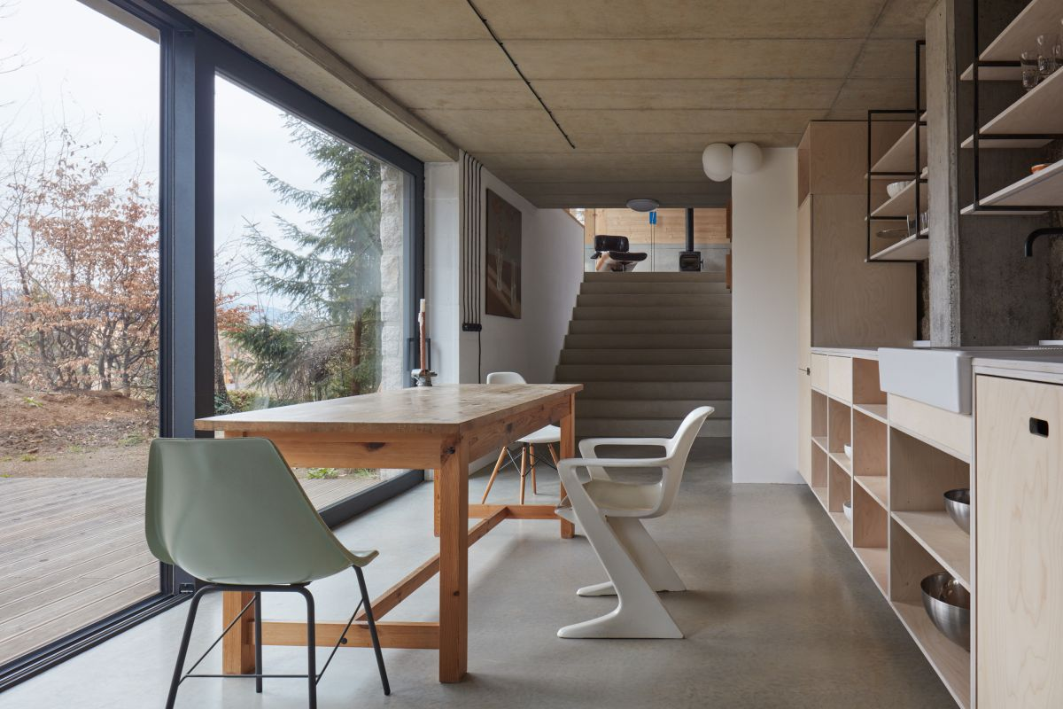 A set of wide concrete stairs connect the kitchen and dining area to the lounge space