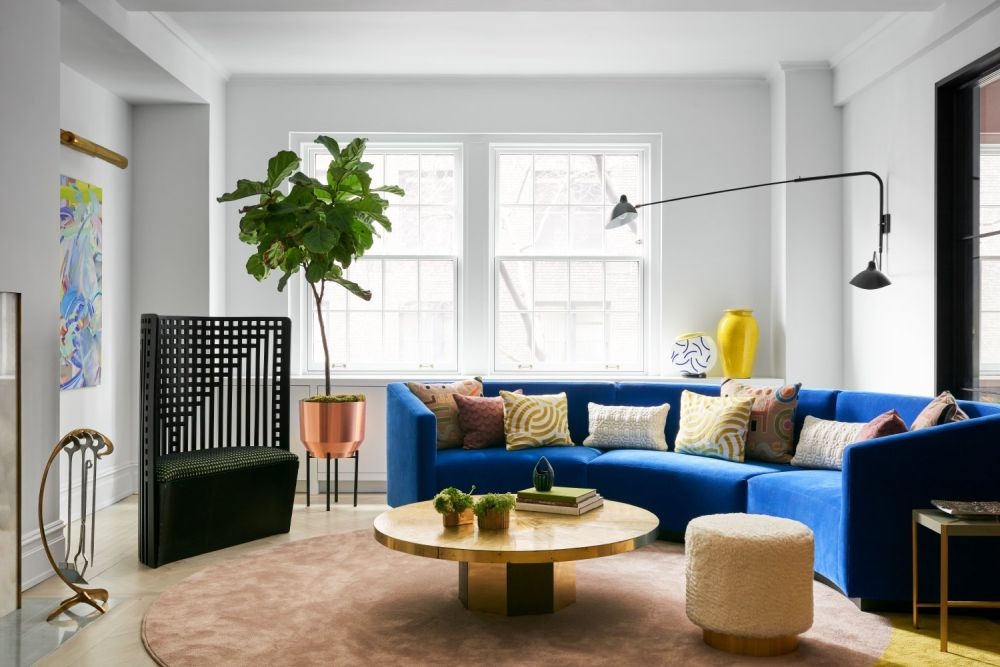 The new living room design is much brighter and has a custom curved sofa as a centerpiece