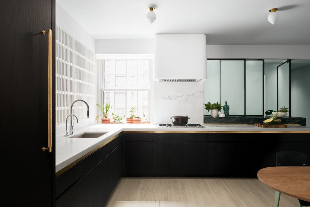 The reimagined kitchen has no upper cabinetry and crisp white walls which better reflect the light