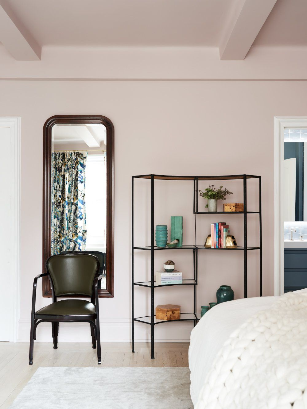 The walls and the ceiling of the bedroom have been painted in a pastel shade of pink which looks very trendy