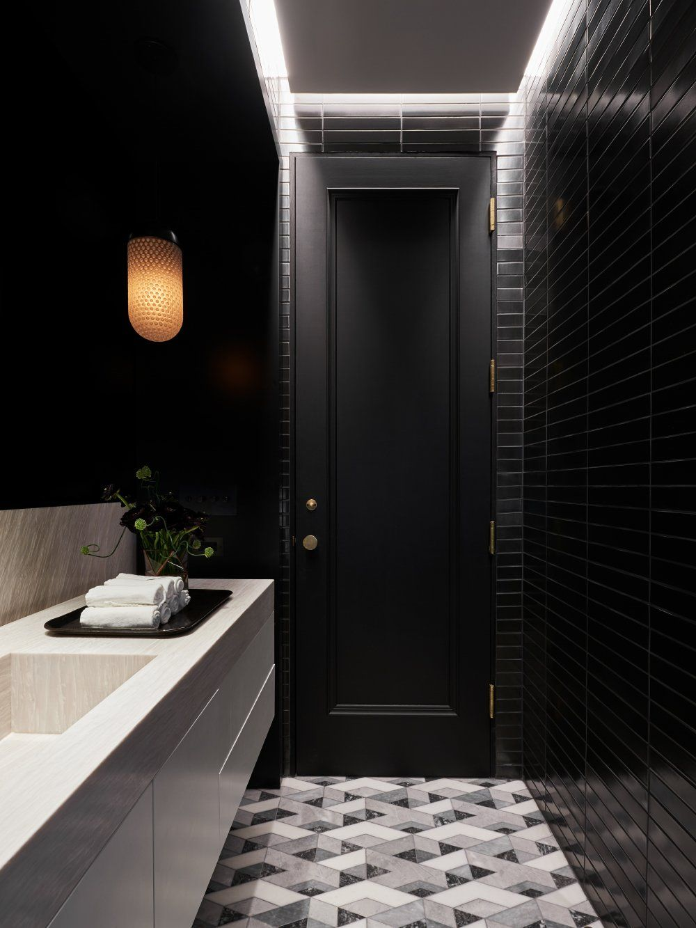 The closet was converted into a powder room with geometric floor tiles and black walls
