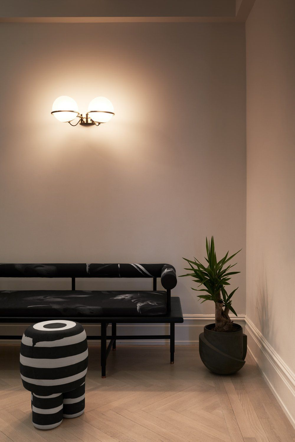 A lighter floor color, muted pink walls and black and white furniture give the entryway a glamorous look