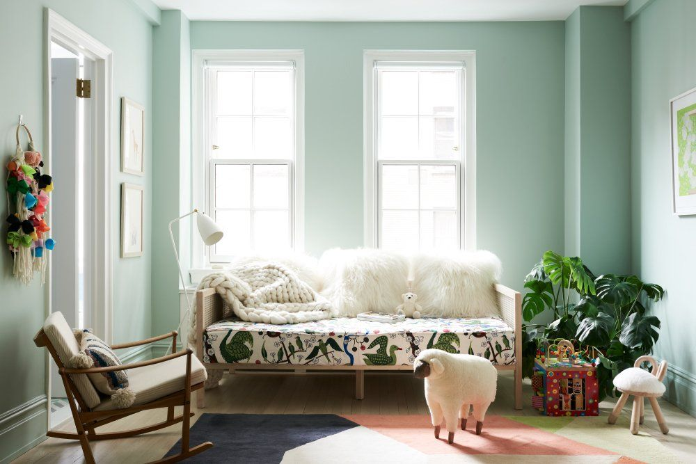 The mint green wall color, casual daybed and rocking chair combo give this bedroom a much fresher vibe