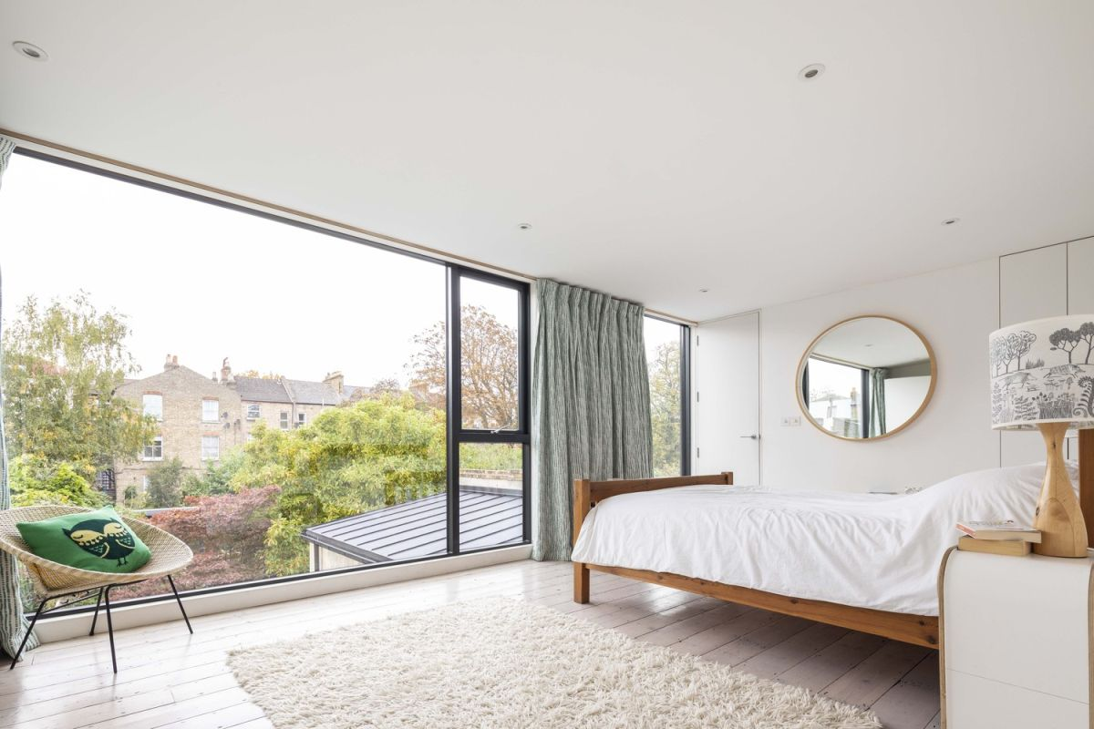 The upstairs bedroom has a huge panorama window with a great view of the garden