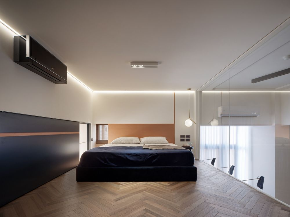 Upstairs the bedroom has herringbone wooden flooring, LED strips marking the ceiling and a glass wall