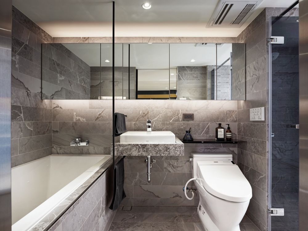 The bathroom has this stone-inspired look, with large backlit mirrors and a warm and welcoming vibe