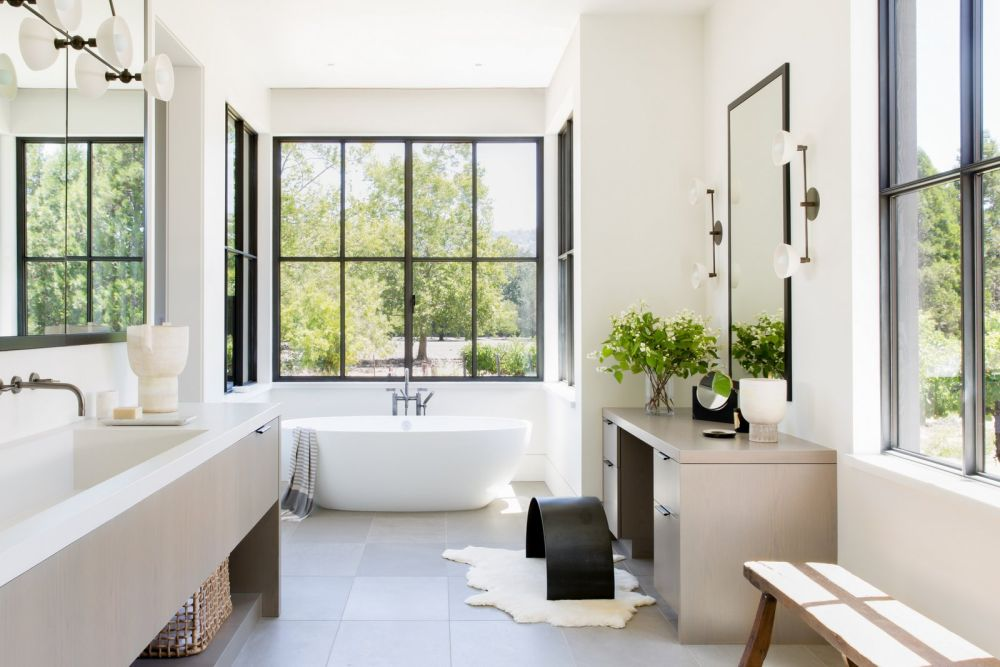 Large mirrors reflect the beautiful views coming through the windows, making the bathroom seem fresh and spacious