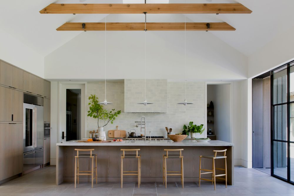 The large open kitchen has direct access outdoors and features a marble-top island with bar seating