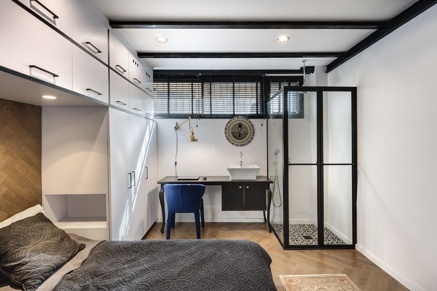 The bedroom has a clear shower area in one of its corners, with a sink table/ desk next to it