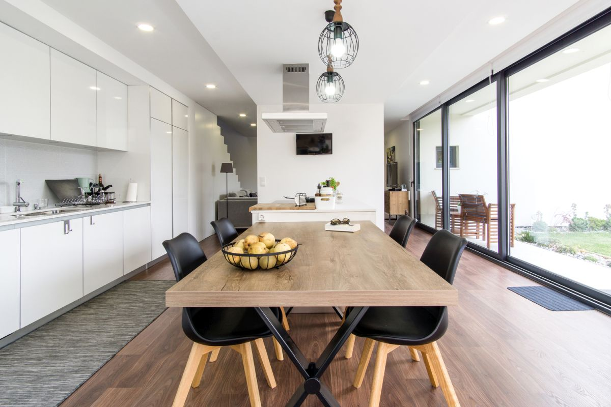 The kitchen and dining area seamlessly merge into one, with a clear distinction in the type of flooring