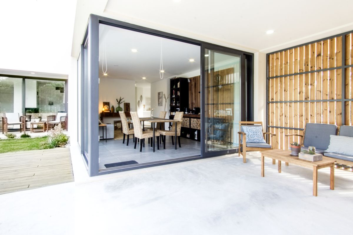 The living spaces have sliding glass doors which connect them to the deck and garden