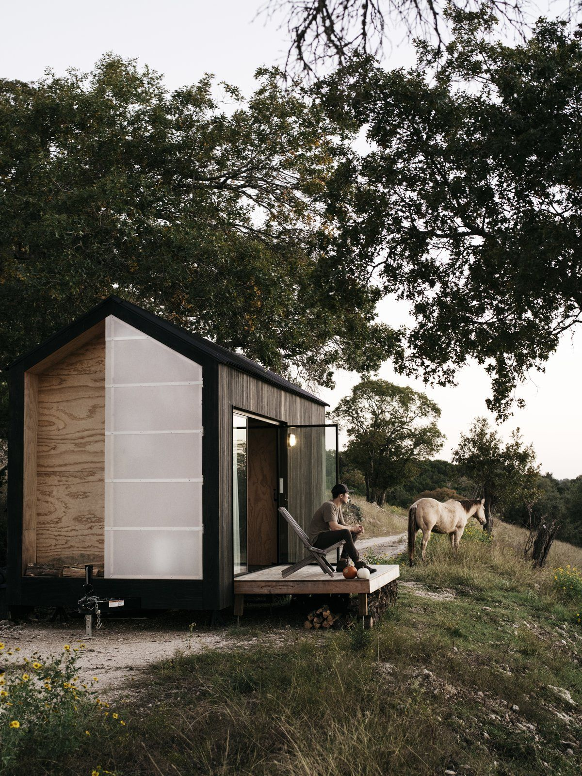 A small wooden deck acts as a connector between the cabin and the landscape