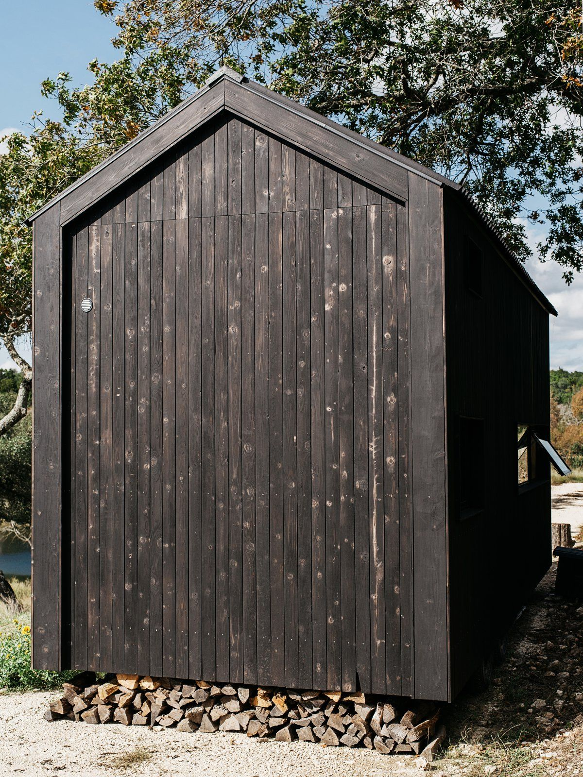 The cabin seems to be floating a few inches above the ground, allowing space for a wood-storage niche underneath