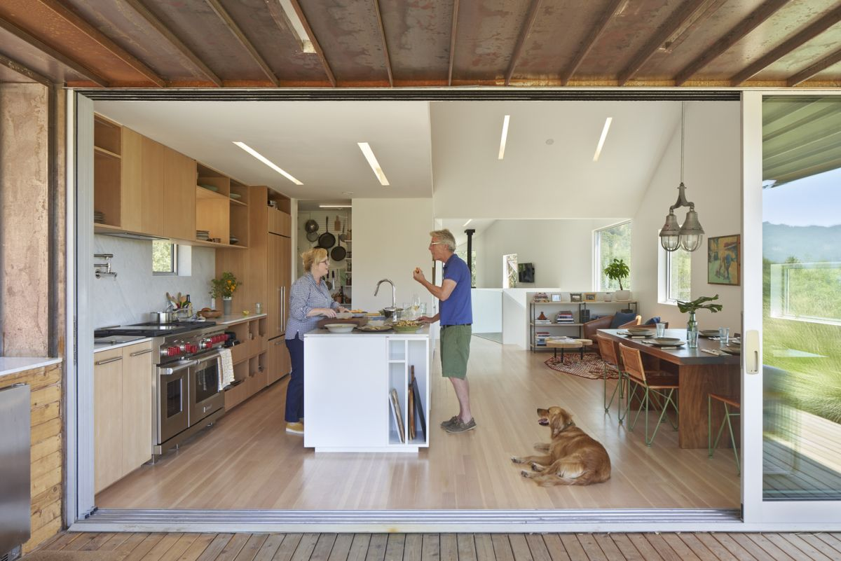 The indoor kitchen extends outside under a cantilevered eave