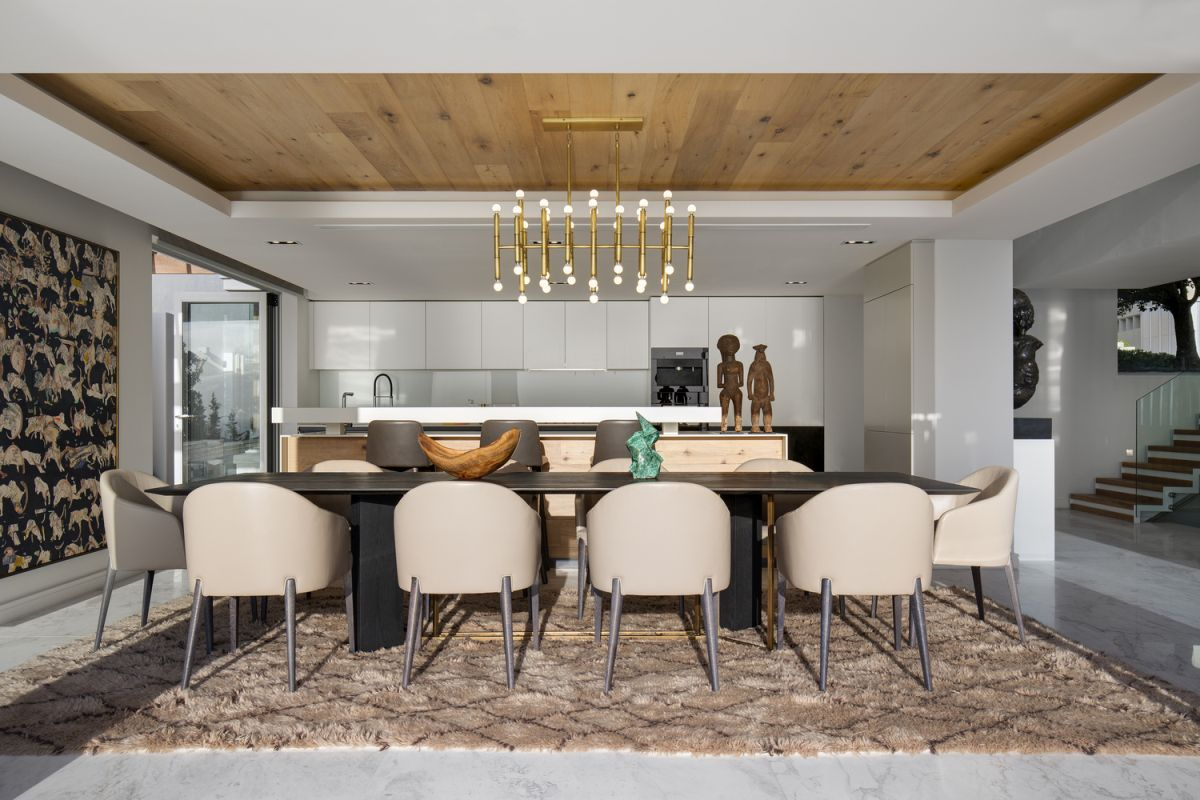 The soft texture of the area rug combined with the metallic chandelier and wooden ceiling looks amazing